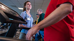 Nursing student monitoring patient on treadmill