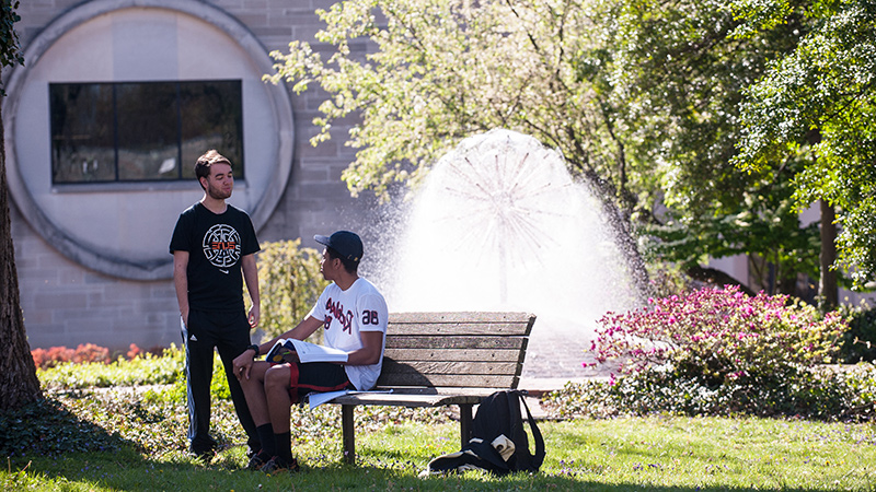 Students sitting next to fountain